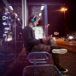 Germany, Munich, man with headphones sitting at bus stop using digital tablet at night